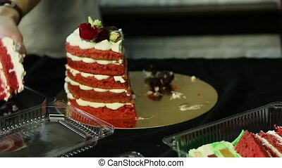 confectioner hands cut down homemade red decorated cake