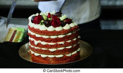confectioner hands cut slowly red decorated cake -...