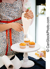confectioner hands topping cupcakes with cream using a pastry bag.