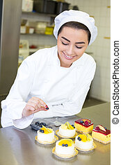 Confectioner preparing cakes at bakery or confectionery - ...