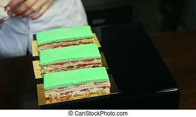 confectioner puts three portions of creamy fruit layered cake with green glaze served on golden stands on black mirror tray