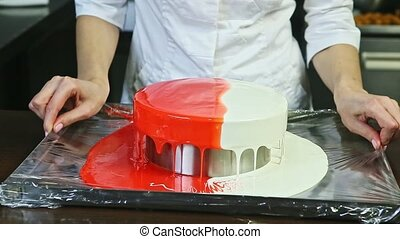 confectioner in white uniform removes excess glaze from colorful glazed round cheesecake over metal stand on kitchen table