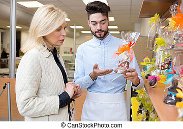 confectioner showing novelty chocolate to customer