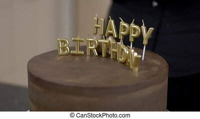 Confectioner shows gold letters on a chocolate cake for the...