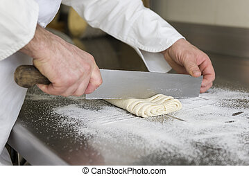 confectioner - pastry chef cuts the dough for preparing...