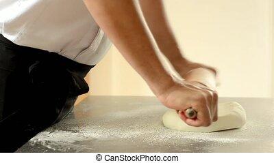 Confectioner using rolling pin preparing fondant for cake...