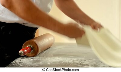 Confectioner using rolling pin preparing fondant for cake...