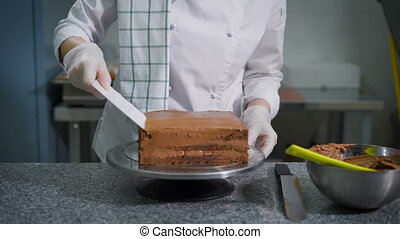 Confectioner with a spatula spread chocolate on a freshly...