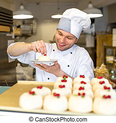 Confectioner with cakes - Handsome confectioner in uniform ...