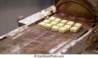 production, candy shop and people concept - confectioner setting candies to chocolate coating machine at confectionery
