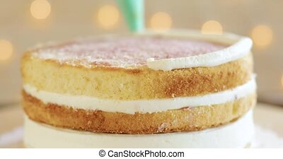 Confectioner woman is pouring cream on sponge cake using ...