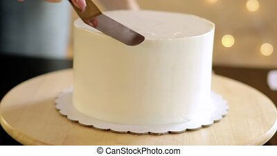 Confectioner woman is smearing cream on top of cake using ...