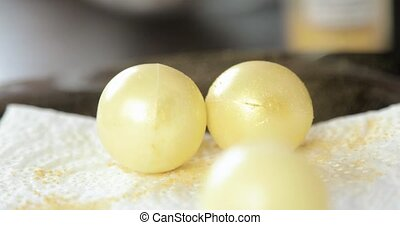 Confectioner woman painting white chocolate balls in golden ...