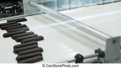 Confectionery factory. Chocolate production. Trays with chocolate bars move along the conveyor. 4K