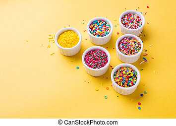 Confectionery sprinkles on a yellow background