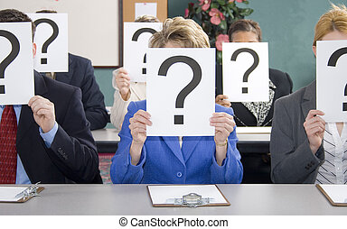 Group of business woman and men sitting at table with question marks held in front of face.