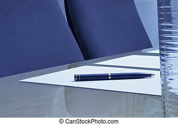 A close-up of a boardroom showing a pen on a piece of paper with a glass of water in the foreground. Sharp focus on the pen.
