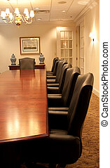 The side of a large conference table with leather chairs along one side