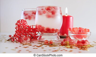 Confetti falling down, slow motion. Two glasses with alcohol decorated with candies, red candle, closeup. Romantic still life isolated on white background. Saint valentine's day celebration.