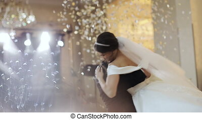 Confetti in the air. Beautiful brunette bride and handsome...