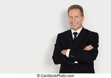confiado, businessman., alegre, hombre maduro, en, formalwear, mantener, armamentos cruzaron, y, sonriente, mientras, posición, contra, gris, plano de fondo