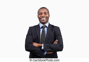 confiado, businessman., alegre, joven, hombre africano, en, formalwear, mantener, armamentos cruzaron, y, sonriente, en cámara del juez, mientras, posición, contra, fondo blanco