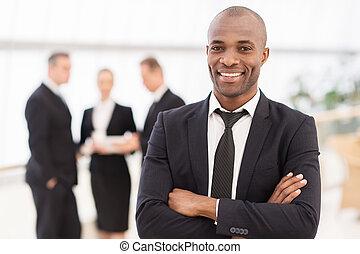 confiado, businessman., alegre, joven, hombre africano, en, formalwear, mantener, armamentos cruzaron, y, sonriente, mientras, el suyo, colegas, posición, fondo