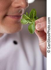 confiado, chef., primer plano, de, chef, oler, menta, y, sonriente