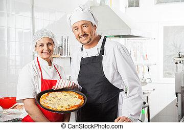 confiado, chefs, con, pizza, cacerola, en, cocina comercial