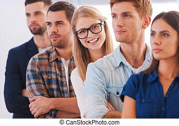 confiado, en, ella, team., atractivo, mujer joven, sonriente, mientras, posición, consecutivo, con, otro, gente