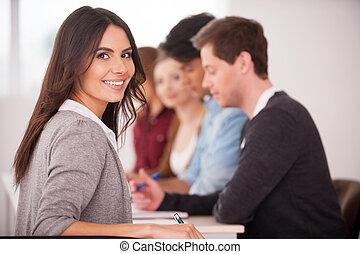confiado, en, ella, team., vista trasera, de, hermoso, mujer joven, mirar hombro, y, sonriente, mientras, el sentarse junto, en la mesa, con, otro, gente