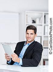 confiado, hombre de negocios, tenencia, tableta de digital, en el escritorio