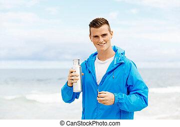 confiado, joven, teniendo botella, con, agua