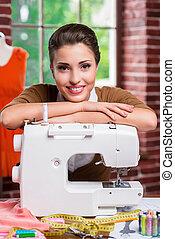 confiado, moda, designer., hermoso, hembra, diseñador de modas, propensión, en, el, máquina de coser, y, sonriente, mientras, sentado, en, ella, lugar activo