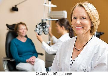 confiado, optometrista, con, colega, examinar, paciente