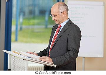 confiado, podio, lectura, maduro, hombre de negocios
