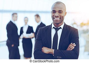 confiado, y, exitoso, businessman., alegre, joven, hombre africano, en, formalwear, mantener, armamentos cruzaron, y, sonriente, mientras, el suyo, colegas, posición, fondo
