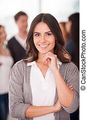 confiant, équipe, leader., beau, jeune femme, tenant main, sur, menton, et, sourire, quoique, groupe gens, debout, arriere-plan