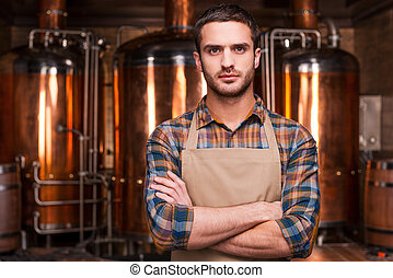 confiant, brewer., confiant, jeune, mâle, brasseur, dans, tablier, garder, bras croisés, et, regarder appareil-photo, quoique, debout, devant, métal, récipients