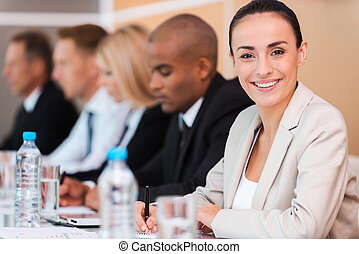 confiant, business, expert., groupe gens affaires, séance, rang, et, écriture, quelque chose, dans, leur, note, coussins, quoique, beau, jeune femme, dans, formalwear, regarder appareil-photo, et, sourire