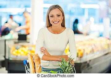 confiant, dans, elle, nourriture, choice., sourire, jeune femme, penchant, à, les, chariot, et, regarder appareil-photo, quoique, debout, dans, a, magasin nourriture