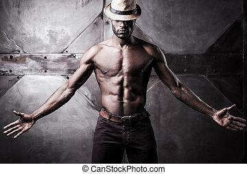 confiant, dans, sien, style., beau, jeune, sans chemise, homme africain, dans, chapeau, étirage, dehors, mains, quoique, debout, contre, métal, fond