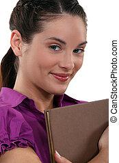confiant, femme souriante, livre, tenue