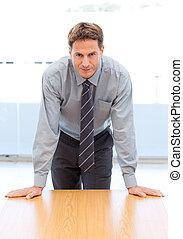 confiant, homme affaires, poser, s'appuyer, a, table