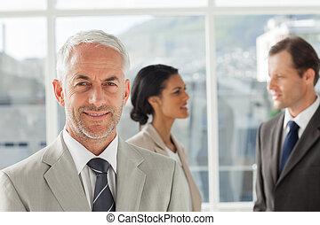 confiant, homme affaires tient, devant, collègues, parler, ensemble, dans, leur, bureau