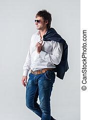 confiant, par, complet, épaule, séduisant, veste, type, tenue, mur, lunettes soleil, jean, gauche, stands, sérieux, sien, regarder loin, contre, côté, frais