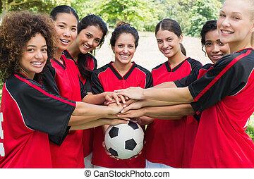 confiante, equipe futebol, empilhando mãos, ligado, bola