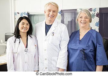 confiante, equipe médica, sorrindo, junto, em, clínica