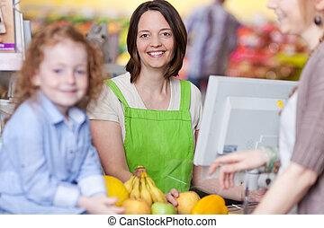 confiante, femininas, caixa, sorrindo, em, supermercado