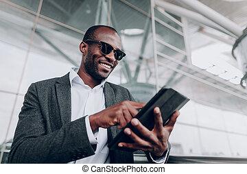 confiante, homem negócios, é, usando, tabuleta, perto, escritório